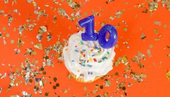 "Cupcake with number candles that say ""10"" on a backround of solid colored orange with gold confetti"